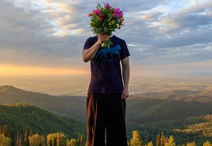 Man_Holding_A_Bouquet_of_Flowers_On_Top_Of_A_Mountain